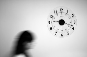 immagine di un orologio su parete bianca con donna sfumata che sta per passargli avanti